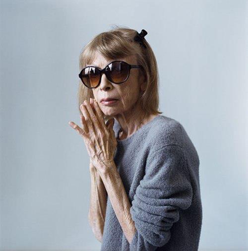 Et billede af Joan Didion der har solbriller på og en grå strik trøje Fotografiet ligner et modefotograi